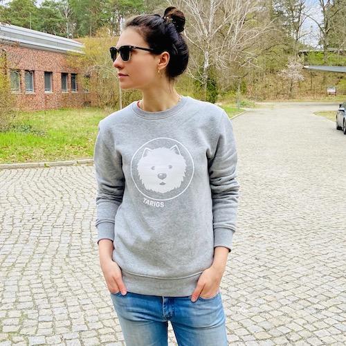 Woman wearing light gray sweatshirt with Westie motif